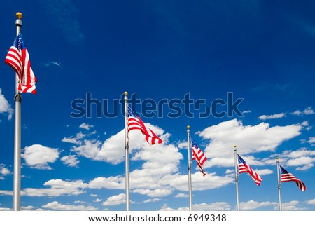 Series of American flags flying in the wind over blue sky with white clouds