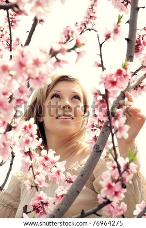 series of close-up portrait of a beautiful woman in the branches of cherry blossoms with pink flowers