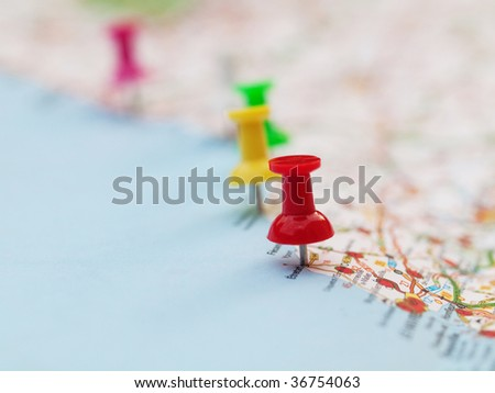 Series of colored pin pointing locations on a french map with selective focus on the red pin