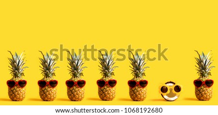 Series of pineapples and a coconut wearing sunglasses on a yellow background