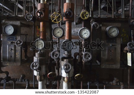 Series of pipes and knobs in an abandoned power plant.