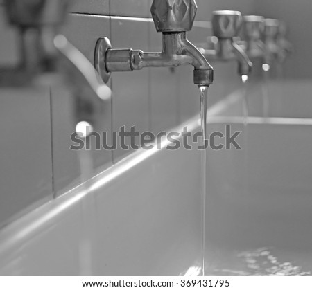 series of stainless steel taps with water coming out of the school in the sink