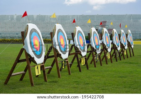Series of straw archery targets in wooden stands inside football stadium