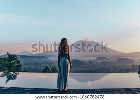 series traveling girl in Asia. beautiful girl with long dark hair in elegant grey dress posing in beautiful nature place in Bali, staying near swimming pool with volcano Agung view