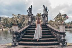 series traveling girl in Asia. beautiful girl with long dark hair in elegant grey dress posing on old bridge in Tirta Gangga water temple in Bali