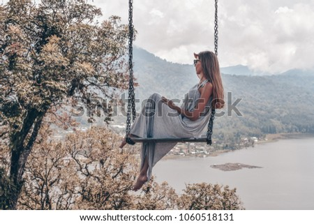 series traveling girl in Asia, beautiful girl with long dark hair in elegant grey dress sitting on the swing in beautiful nature place in Bali