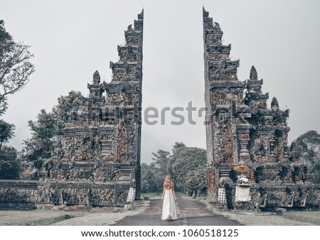 series traveling girl in Asia. Old indonesian gate. beautiful girl with long dark hair in elegant grey dress posing in beautiful nature place in Bali.