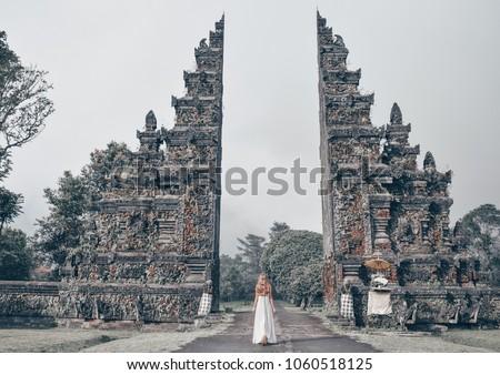 series traveling girl in Asia. Old indonesian gate. beautiful girl with long dark hair in elegant grey dress posing in beautiful nature place in Bali.