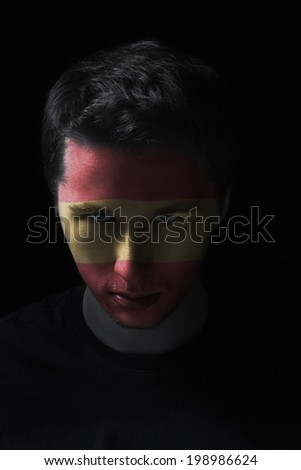 serios man face with painted flag colors of Spain, black background
