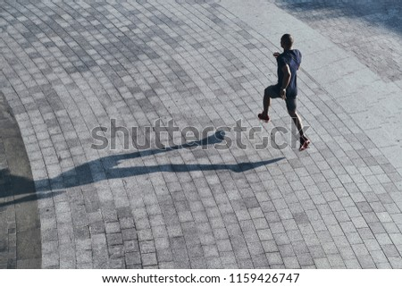 Serious about staying in shape. Top view of young African man in sports clothing jogging while exercising outdoors #1159426747