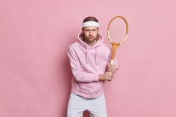 Serious active sportsman stands with tennis racket plays favorite game goes in for sport for health dressed in active wear enjoys active leisure isolated over pink background challenging himeself