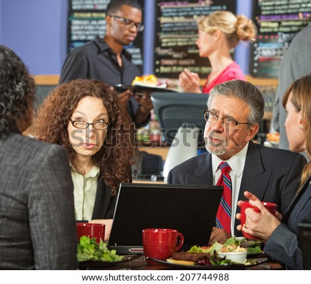 Serious adult business people meeting at indoor cafe