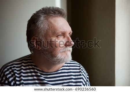 Serious adult man with grey hair looking into the window