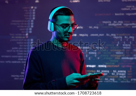 Serious advanced young Arabian tester in wireless headphones examining new app on gadget, coding background Сток-фото ©