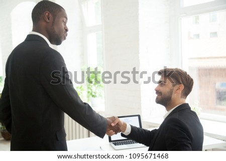 Serious African American boss handshaking congratulating proud Caucasian subordinate with closing profitable deal, successful business strategy, good personal job, achievements, welcoming new member
