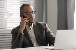 Serious African American businessman in glasses talking on phone, using laptop, having business conversation, hr manager holding interview by cellphone, employee consulting client, making sell offer