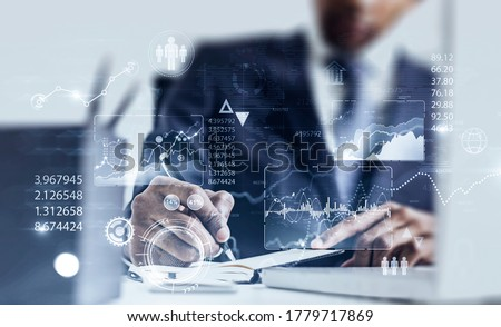 Serious African American businessman working in blurry office with double exposure of HUD infographic interface. Concept of statistics and data analysis. Toned image