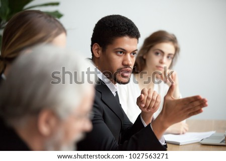 Serious african american ceo giving instructions at diverse team meeting, confident black leader talking delegating work, serious dark-skinned executive manager speaking appealing to colleagues group