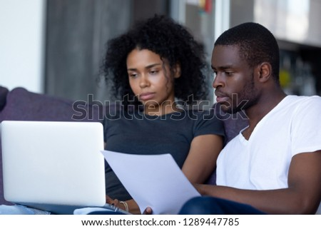 Serious african american couple reading document letter pay domestic bills checking bank account online on laptop at home, black family holding paper planning budget money expenses with computer app