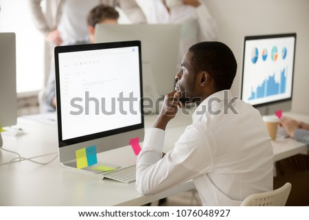 Serious african american employee thinking over business email working on computer in office, focused puzzled black manager looking at screen reading or writing electronic letter to corporate client