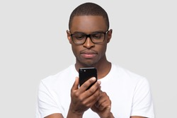 Serious African American man in glasses looking at phone screen, using mobile device apps, surfing internet, chatting with friends in social network, playing game, isolated on studio background