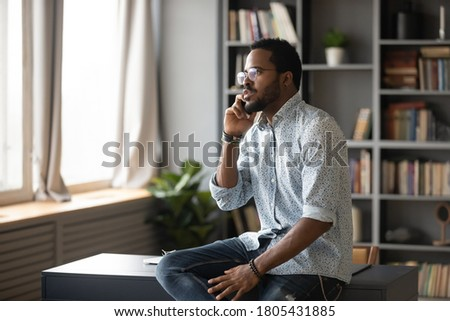 Serious African American man wearing glasses talking on phone, making call, sitting on work desk, confident businessman consulting client customer by cellphone, negotiating with partners Foto stock ©