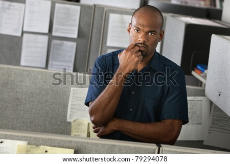 Serious African-American man with his hand on chin stands in his office cubicle