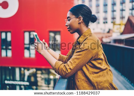 Serious African American woman in casual wear checking mail on cellphone connected to 4G internet on urban setting,dark skinned hipster girl texting message in chat, surfing blog via smartphone
