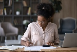 Serious African American woman in glasses calculating expenses, using calculator, sitting at desk with laptop and financial documents, focused young female managing planning household budget