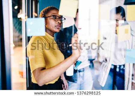 Serious african american woman writing on glass during workshop in coworking space, professional female coach making notes of information during workflow planning strategy for startup project