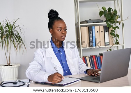 Serious african female doctor watching online medical webinar seminar training elearning on laptop make notes. Black woman physician gp participate video conference call videoconferencing on computer.