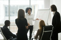 Serious african female leader or coach gives presentation of new marketing plan at sales team meeting, black employee explains colleagues new client management strategy idea at group office training