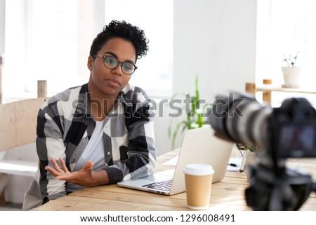 Serious african girl blogger vlogger talking to camera shooting educational video filming webinar blog, black female business coach teacher speaking recording vlog training or job interview