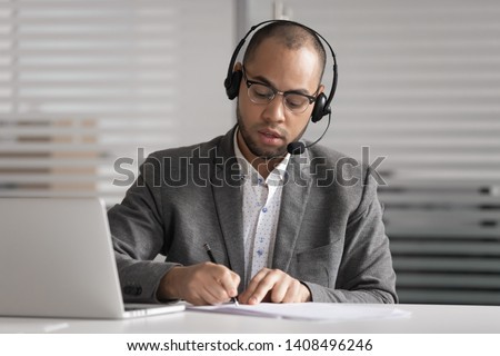 Serious african male customer support service agent wear wireless headset talk write notes make video conference call, focused mixed race businessman operator representative  online chat