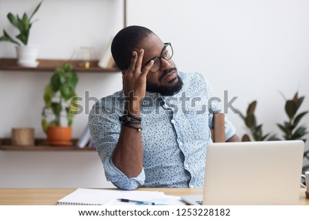Serious african millennial businessman thinking cogitating about business issues. Frustrated black entrepreneur searching problem solution sitting alone on chair at modern office desk looking away