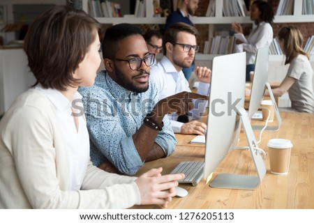 Serious african office worker explaining coworker new online project, diverse colleagues discuss idea working together on computer in office, black mentor helping colleague with pc in coworking space
