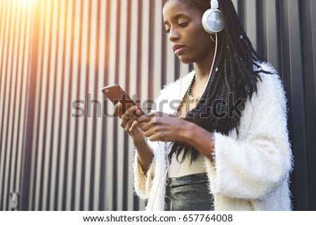 Serious afro american hipster girl using application for listening songs from playlist while chatting standing on promotional background, attractive female black model enjoy radio broadcasting