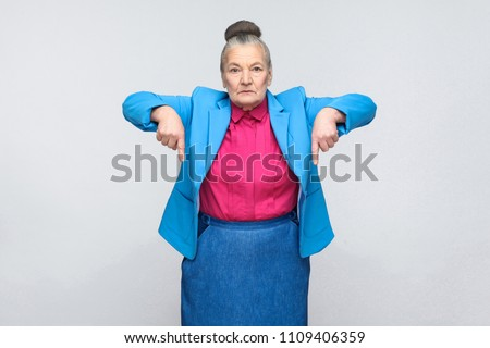 serious aged woman pointing fingers at copy space. Portrait of expressive grandmother with light blue suit and pink shirt standing with collected bun gray hair. Studio shot isolated on gray background #1109406359