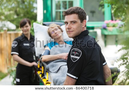 Serious ambulance worker with patient on stretcher - stock photo