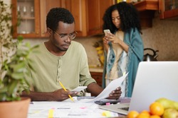 Serious and concentrated young African-American male wearing spectacles paying bills online, using banking app on his mobile phone. People, paperwork, finances, family budget and economy concept