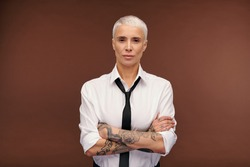 Serious and confident blond businesswoman in formalwear crossing arms with tatoos by chest while standing in front of camera in isolation