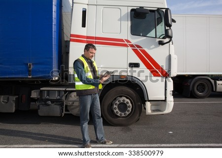 Serious and confident Man standing in front of truck #338500979