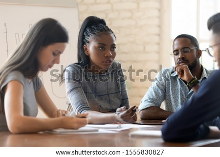 Serious anxious colleagues gathered together in boardroom solve work issues, multi racial businesspeople african caucasian mates during briefing meeting in office, teamwork problems discussion concept