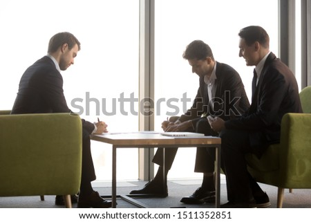 Serious Arabian businessman signing contract, partnership agreement with business partner in office, business people making deal after successful negotiation, candidate putting signature on document