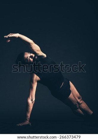 Serious Athletic Man with Long Goatee Beard Doing a Floor Exercise, Performing Side Plank, A Powerful Arm and Wrist Strengthener Pose. Captured in Studio on Black Background