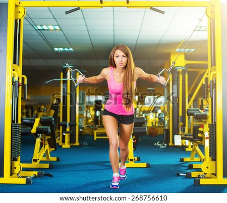 serious athletic woman pumping up muscles in a gym