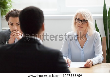 Serious attentive senior female hr manager employer listening to candidate at job interview, focused strict mature businesswoman thinking about hiring decision at difficult group negotiations concept