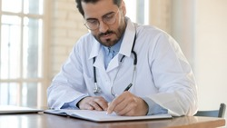 Serious attentive young male doctor qualified specialist surgeon therapist focused on filling patient chart, thinking on diagnosis definition in records, studying materials to write scientific article