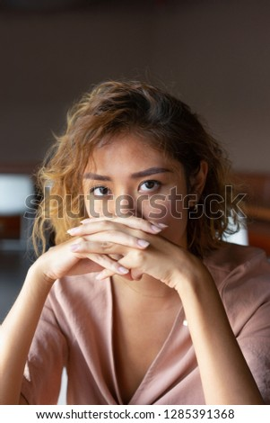 Serious attractive lady with curly hair leaning on hands. Introspective young Chinese woman looking at camera. Deep in thoughts concept