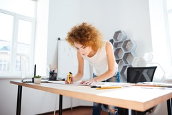 Serious attractive young woman photographer with curly red hair working in office using stationery knife